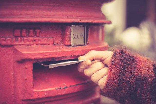 赤いポストと女性の手